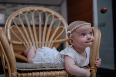 A portrait of a five-month baby girl with clear blue eyes in a white dress and pearly headband. The child lies on a rattan chair Royalty Free Stock Image