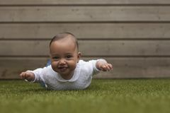 Portrait of a five months old baby girl lying on her belly outside on artificial grass stock photo