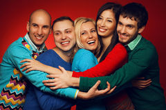 Portrait of five stylish close friends hugging. And posing over red background. Guys having fun. Shiny smile and white healthy teeth. Hipster style. Studio shot royalty free stock photo
