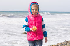 Portrait of a five year old girl with an apple on beach Stock Images