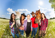 Portrait of five young happy horseback riders. Standing in a row with their horses, in the field at sunny day Royalty Free Stock Image