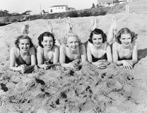 Portrait of five young women lying on the beach and smiling. (All persons depicted are no longer living and no estate exists. Supplier grants that there will be Stock Photos