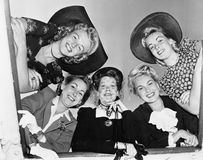 Portrait of five young women smiling and looking down Stock Images