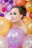 Portrait of flirty brunette posing with balloons Stock Image