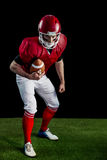 Portrait of focused american football player being ready to attack. On american football field Stock Photo