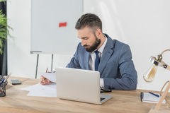 Focused businessman doing paperwork at workplace in office Royalty Free Stock Photography