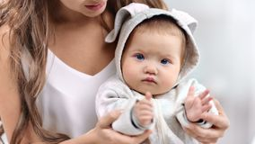 Portrait of focused cute baby wearing white clothes clapping hand looking at camera close-up. Happy family mother and little child playing together feeling stock video footage