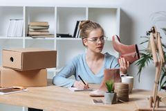 portrait of focused entrepreneur with pair of shoes and notebook working at table stock photos