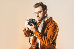 Portrait of focused handsome man with photo camera in hands looking away. Isolated on beige Royalty Free Stock Photo