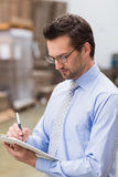 Portrait of focused manager writing on his clipboard. In warehouse Stock Image