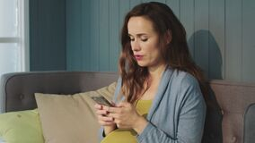 Portrait of focused pregnant woman chatting on smartphone at home. stock video footage
