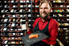 Portrait of food seller. Portrait of a seller or sommelier with wine bottle and salmon on the board at the luxury supermarket or restaurant. Choosing wine Royalty Free Stock Photography