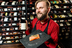 Portrait of food seller. Portrait of a seller or sommelier with wine bottle and salmon on the board at the luxury supermarket or restaurant. Choosing wine Stock Photos