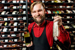 Portrait of food seller. Portrait of a seller or sommelier with wine bottle and trout fish at the luxury supermarket or restaurant. Choosing wine according to Stock Photography