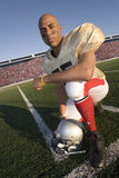 Portrait of football player kneeling on field stock photography