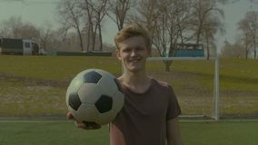 Portrait of footballer with soccer ball on the pitch stock video footage