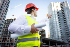 Portrait of foreman with blueprints pointing hand at building Stock Images