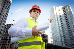 Portrait of foreman in helmet showing building site under constr Royalty Free Stock Photos