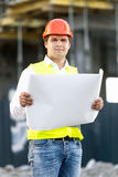 Portrait of foreman reading blueprints on building site Royalty Free Stock Photos