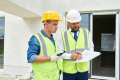 Construction Supervisor Talking to Worker. Portrait of foreman and supervisor discussing construction documents on site, both wearing hardhats and reflective royalty free stock photo