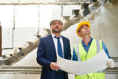 Businessman on Construction Site. Portrait of foreman and supervisor discussing floor plans on site standing by unfinished flight of stairs Royalty Free Stock Photos