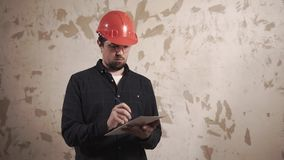 Builder is checking an old apartment. Portrait of foreman wearing protective hat and a mask in the apartment building. He looks around and writes down stock video footage