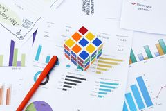 Portrait of fountain pen and Rubik`s cube on the financial paper stock photos
