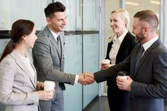 Business People Shaking Hands in Hall stock image