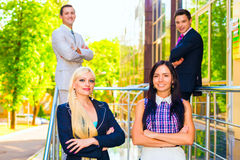 Portrait of four business people. Looking at camera with female leader in front Royalty Free Stock Photos