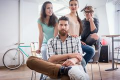 Four co-workers wearing casual clothes during work in a modern hub. Portrait of four co-workers smiling and looking at camera, while wearing cool casual clothes Royalty Free Stock Image