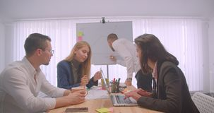 Portrait of four collleagues meeting and having a discussion on the workplace indoors. Businessman drawing a graph on