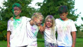 Portrait of four friendly kids: two boys and two blond girls standing in front of the camera hugging each other and stock video footage