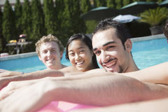 Portrait of four friends in the pool with an inflatable raft Royalty Free Stock Photo