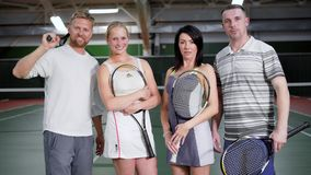 Portrait of four happy friends dressed in sport outfit standing with rackets in recreation area looking at camera. Two stock video