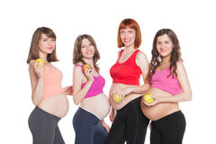 Portrait of four happy pregnant women with fruits Stock Image