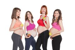 Portrait of four happy pregnant women with fruits Stock Photos