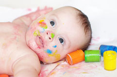 Portrait of four-months baby with multi-colored paints Royalty Free Stock Photos