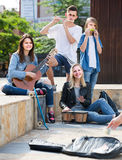 Portrait of four teenagers playing music together outdoors Stock Image