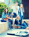 Portrait of four teenagers playing music together outdoors Royalty Free Stock Images
