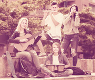 Portrait of four teenagers playing music together outdoors. Portrait of four happy american  teenagers playing music together outdoors Stock Photography