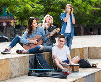 Portrait of four teenagers playing music together outdoors. Portrait of four smiling european  teenagers playing music together outdoors Stock Photo