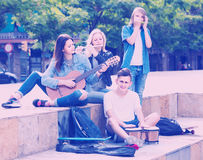 Portrait of four teenagers playing music together outdoors. Portrait of four smiling european  teenagers playing music together outdoors Stock Photography