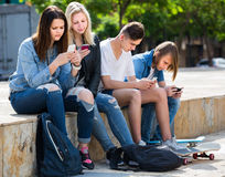 Portrait of four teenagers sitting with their mobile phones outdoors