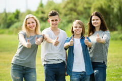 Portrait of four teenagers standing and holding thumbs up together outdoors