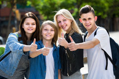 Portrait of four teenagers standing and holding thumbs up togeth Stock Photos