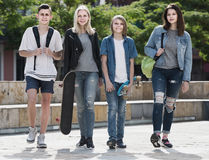 Portrait of four teenagers walking together in town on summer da Stock Images