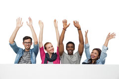 Portrait of four young friends raising hands Stock Photos