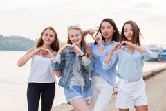 Portrait of four young student girls showing finger gesture heart. Beautiful happy young women on the waterfront royalty free stock photo