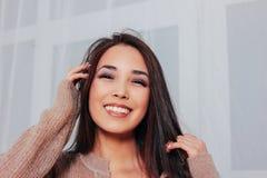 Portrait franc de jeune femme asiatique de sourire sensuelle de fille avec de longs cheveux foncés dans le chandail beige confort photos stock