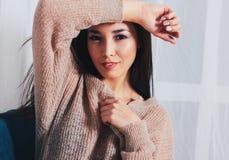Portrait franc de jeune femme asiatique de sourire sensuelle de fille avec de longs cheveux foncés dans le chandail beige confort photographie stock libre de droits